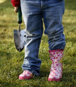 Picture of child with shovel and rubber boots